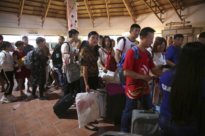 Passagiere stehen bei Ankunft auf der Insel in einer Warteschlange.          Bild      Aaron Favila  AP  dpa