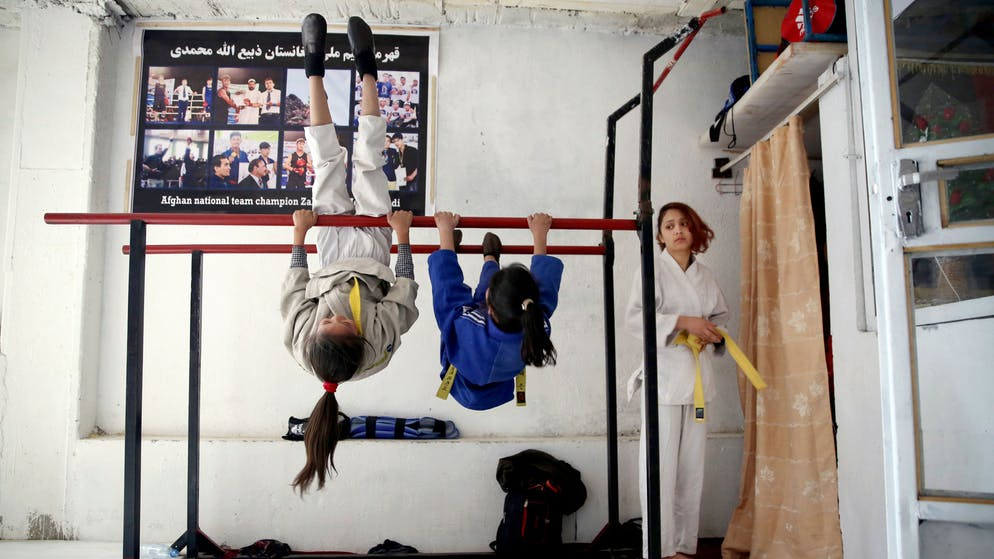 Girls play on a bar ahead of their training session at a Jiu Jitsu club in Kabul, Afghanistan, Saturday, Feb. 15, 2020. In war-torn Afghanistan gender discrimination has deep cultural and historical roots and many women suffer from domestic violence, jujitsu seems an ideal sport for women, it teaches a person self-defense when faced with a stronger and heavier opponent by using specific techniques, holds and principles of leverage. Under the Taliban, women were not allowed to go to school, work outside the home or leave their house without a male escort. (AP Photo/Tamana Sarwary)