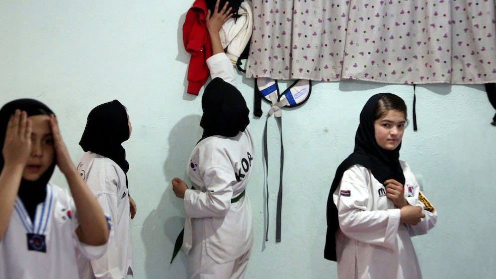 Taekwondo club members athletes get dressed ahead of their practice in Kabul, Afghanistan, Saturday, Feb. 23, 2020. In war-torn Afghanistan gender discrimination has deep cultural and historical roots and many women suffer from domestic violence, jujitsu seems an ideal sport for women, it teaches a person self-defense when faced with a stronger and heavier opponent by using specific techniques, holds and principles of leverage. Under the Taliban, women were not allowed to go to school, work outside the home or leave their house without a male escort. (AP Photo/Tamana Sarwary)