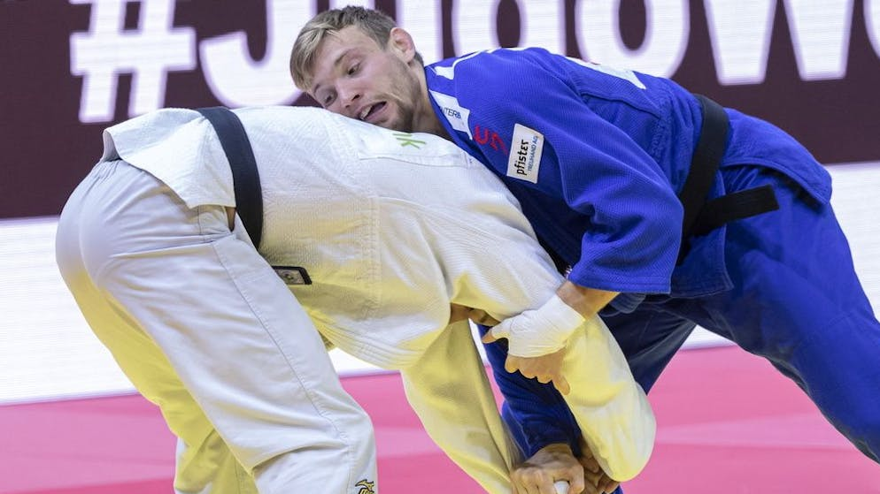 epa09254631 Nils Stump (in blue) of Switzerland in action against Aden-Alexandre Houssein (in white) of Djibouti in the men's -73kg category of the World Judo Championships in Papp Laszlo Budapest Sports Arena, Budapest, Hungary, 08 June 2021. EPA/Zsolt Szigetvary
