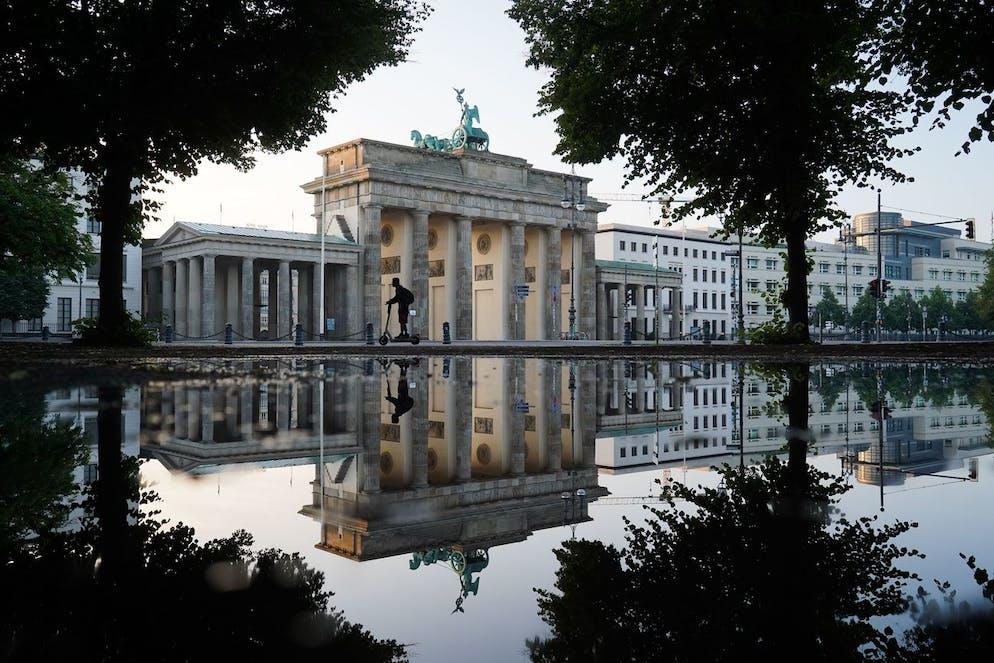 16 juillet 2021, Berlin : un homme conduit un e-sooter au lever du soleil tandis que la porte de Brandebourg se reflète dans une flaque d'eau.