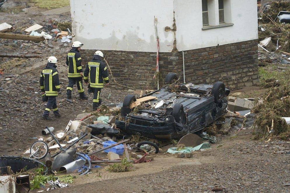 Les pompiers passent devant une voiture détruite dans la communauté de Schuld, en Allemagne, le vendredi 16 juillet 2021.