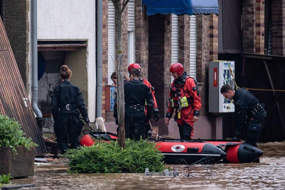 16 juillet 2021, Rhénanie du Nord-Westphalie, Erfstadt : des sauveteurs et des plongeurs de la police utilisent un canot pneumatique pour entrer dans une cour intérieure inondée.