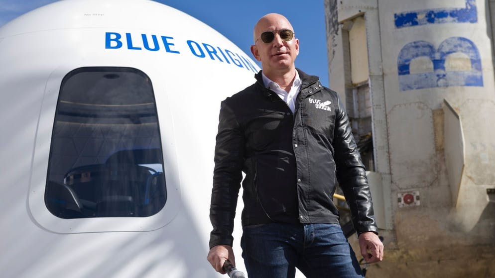 Billionaire Jeff Bezos stands in front of a space capsule at the Space Symposium in Colorado Springs.