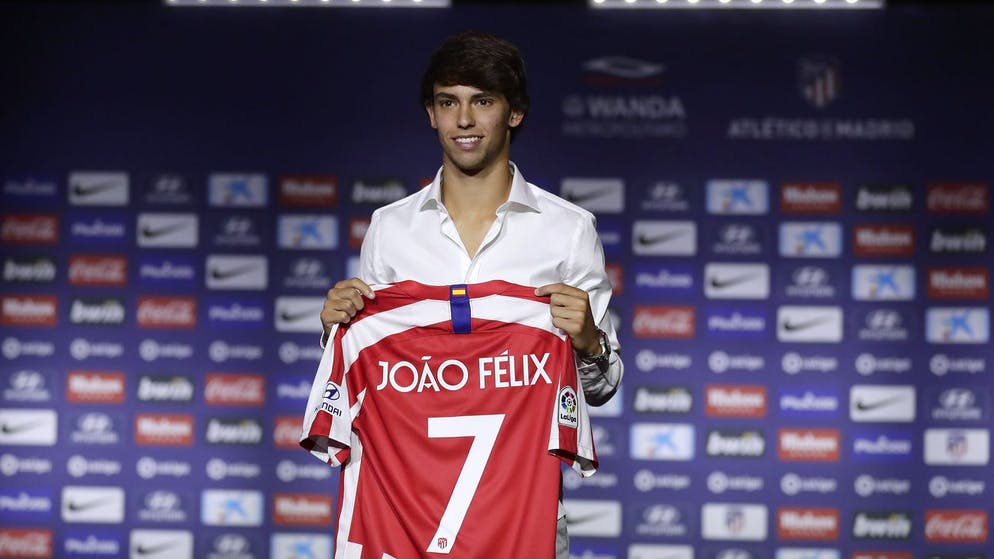 Atletico Madrid's new signing soccer player Joao Felix holds his new jersey as he poses for media during his official presentation at the Wanda Metropolitano Stadium in Madrid, Monday, July. 8, 2019. Atletico Madrid has reached a deal to sign Joao Felix and will sign a seven-year contract. (AP Photo/Manu Fernandez)