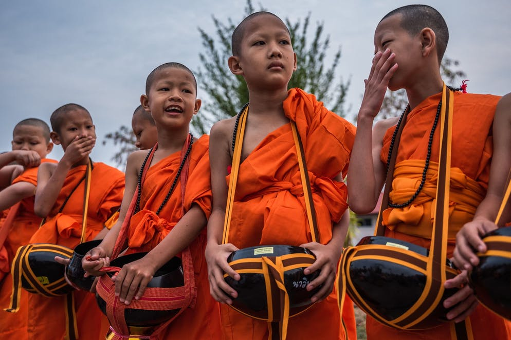 Poy Sang Long is over. The ordinary boys have turned into princes into novices. The day after ordination.   Today, Nawin Nanit (10 years old Nawin) and the other early risers will now learn how to collect alms from the nearby villagers. In Theravada Buddhism, alms is the respect given by a devoted Buddhist to the novice, a monk or a nun. On a daily basis, the monkhood sets off for an alms round, mostly to collect food. This is often perceived as giving the laypeople the opportunity to make merit These donations are likely mistaken for charity, even though they are rather a symbolic connection to spirituality. The paradox in Buddhism is that the more a person contributes without seeking something in return – the wealthier and luckier one will become. Thus, many make use of the monkhood to outsource their own dilemmas by getting blessed for their generosity. By giving alms one destroys those acquisitive impulses that ultimately lead to further suffering.