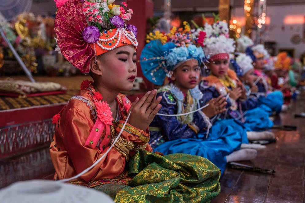 """Nawin Nanit, 10 years old, holds on to the Sai Sin during a ceremony in Wat Klang Thung.  Sai Sin. The white cotton thread is present at formal buddhist ceremonies all over Thailand, weddings and funerals alike, but also when people move into a new home. At larger gatherings like Poy Sang Long there is often one big ball of thread which is tied first around a Buddha image before being passed along through the folded hands (Wai) of the participants. Sai Sin is supposed to evoke protective powers, boosting protection and health to those holding or wearing it. The chanting of the monkhood and associated merit is then symbolically flowing through the thread reaching all those being connected to the thread.   During Poy Sang Long the boys (between 7-14 years of age) are being dressed up to the nines in imitation of Gautama Buddha's son Rahun. Historical tales indicate that Gautama Siddhartha (who became later Buddha) was a prince when he set off for self-discovery. Nevertheless, referring to the Tripitaka (the Buddhist almanac) Buddha himself has never been ordinated, thus the Sang Long follow the path of Buddha's son Rahun. Outside, the """"Tapae"""" (helpers/ carriers) are patiently waiting for the boys to come, as they will be responsible to carry the jeweled princes (Sang Long) on their shoulders from temple to temple. The short-lived royals, just like real princes and kings, are not allowed to touch the ground – at least not until they will enter the monastery life as novices on the final day of Poy Sang Long."""