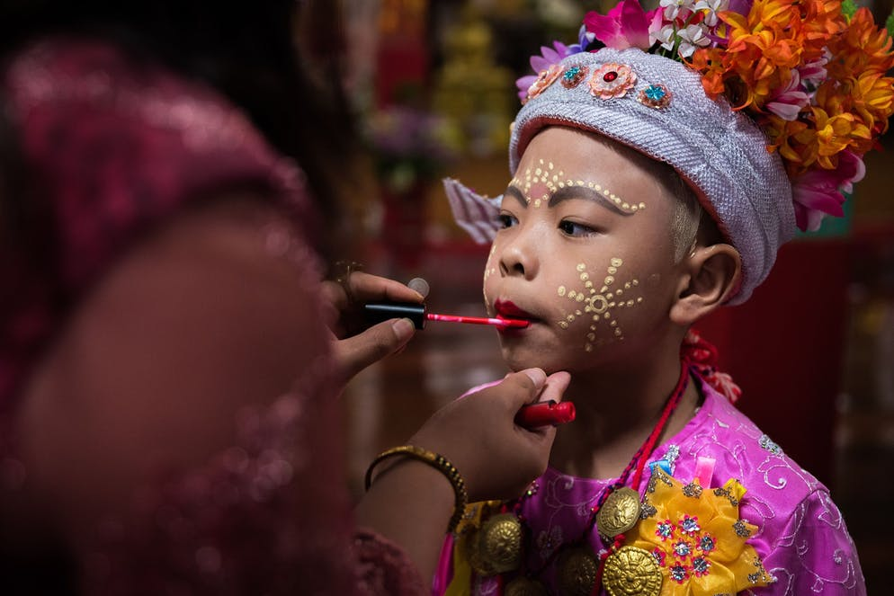 """At dawn, the mothers are already busy applying some burgundy gloss on their sons' innocent lips. Right after the make up, the Sang Long are getting wrapped in festive dresses, and adorned with traditional jewelry such as rings, necklaces, bracelets, and last but not least; the crown decorated with colorful flowers.   During Poy Sang Long the boys (between 7-14 years of age) are being dressed up to the nines in imitation of Gautama Buddha's son Rahun. Historical tales indicate that Gautama Siddhartha (who became later Buddha) was a prince when he set off for self-discovery. Nevertheless, referring to the Tripitaka (the Buddhist almanac) Buddha himself has never been ordinated, thus the Sang Long follow the path of Buddha's son Rahun. Outside, the """"Tapae"""" (helpers/ carriers) are patiently waiting for the boys to come, as they will be responsible to carry the jeweled princes (Sang Long) on their shoulders from temple to temple. The short-lived royals, just like real princes and kings, are not allowed to touch the ground – at least not until they will enter the monastery life as novices on the final day of Poy Sang Long."""