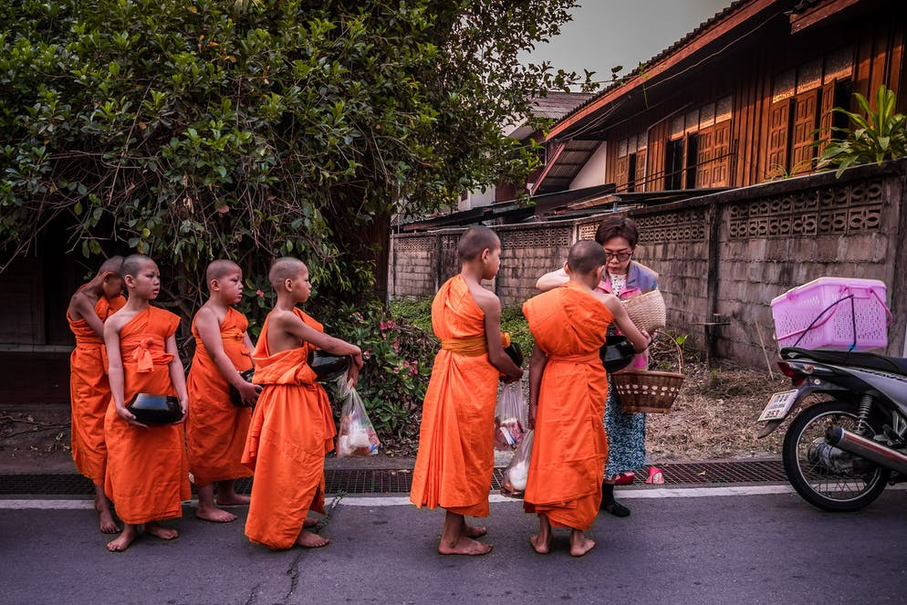 Poy Sang Long is over. The ordinary boys have turned into princes into novices. The day after ordination. Ancient practice of Buddhist alms collecting/giving. The novices awake early and venture barefooted through the town of Mae Hong Son in search for food. They'll eventually return after some 2-3 hours with their bowls packed with essentials for the day. Only sometimes, during special occassions, lay people will give money for the monastery.  Today, the early risers will now learn how to collect alms from the nearby villagers. In Theravada Buddhism, alms is the respect given by a devoted Buddhist to the novice, a monk or a nun. On a daily basis, the monkhood sets off for an alms round, mostly to collect food. This is often perceived as giving the laypeople the opportunity to make merit These donations are likely mistaken for charity, even though they are rather a symbolic connection to spirituality. The paradox in Buddhism is that the more a person contributes without seeking something in return – the wealthier and luckier one will become. Thus, many make use of the monkhood to outsource their own dilemmas by getting blessed for their generosity. By giving alms one destroys those acquisitive impulses that ultimately lead to further suffering.