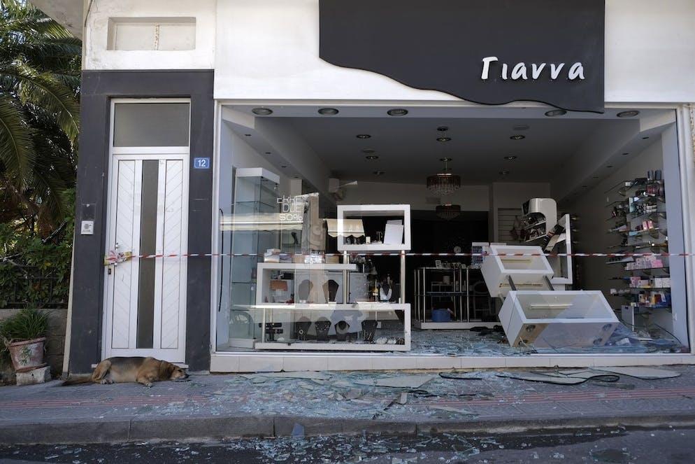 Un chien se trouve à côté d'un magasin endommagé après un violent tremblement de terre dans le village d'Arkalochori sur l'île méridionale de Crète, en Grèce, le lundi 27 septembre 2021.
