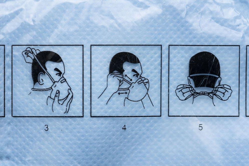 Eine Anleitung fuer das korrekte Aufsetzen einer FFP2 Atemschutzmaske, fotografiert am 25. Maerz 2020 in Zuerich. (KEYSTONE/Christian Beutler)