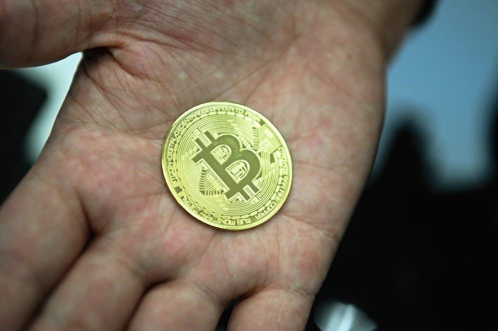 ARCHIV - 17.12.2019, Bayern, Bamberg: Ein Mann hält eine nachgemachte Münze mit dem Bitcoin-Logo in den Händen. (zu dpa «Bitcoin steigt erstmals über 25 000 US-Dollar») Foto: Nicolas Armer/dpa +++ dpa-Bildfunk +++ (KEYSTONE/DPA/Nicolas Armer)