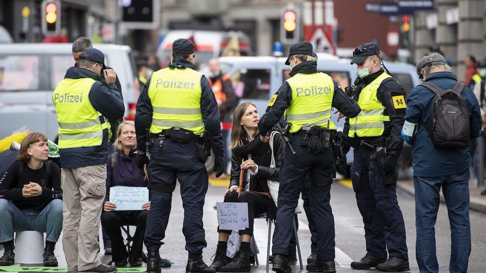 Polizisten kontrollieren die Aktivisten der Klimaorganisation