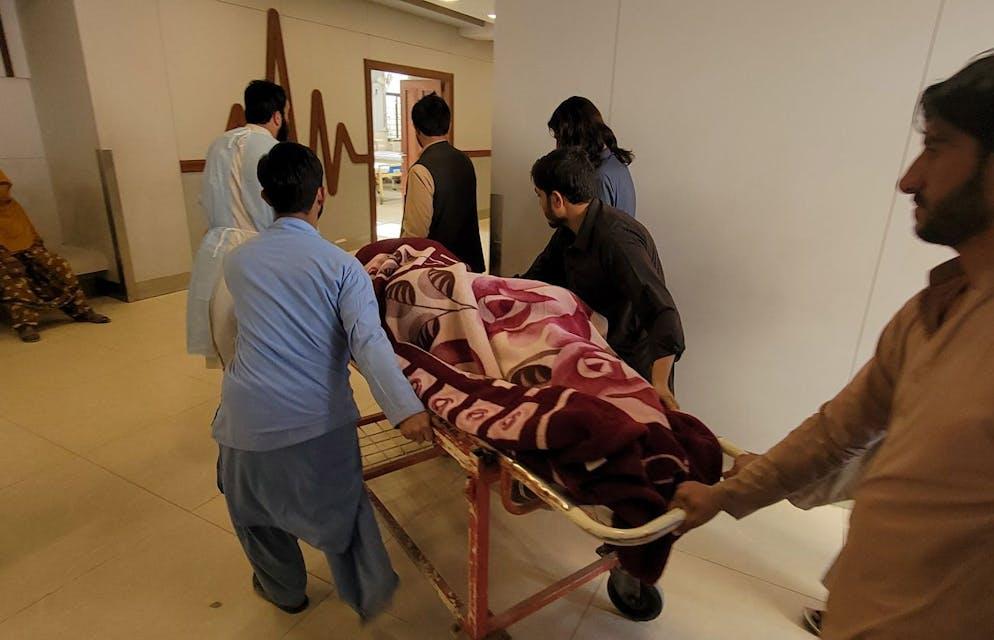 Les gens déplacent une victime blessée, après qu'un séisme de magnitude 5,9 avec une faible profondeur de 9 kilomètres a frappé Harnai, vers un hôpital de Quetta.