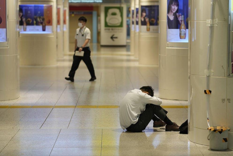 Un homme est assis sur le sol de la gare de Tokyo lorsque tous les services ferroviaires ont été suspendus depuis la gare de Tokyo le jeudi 10 octobre.