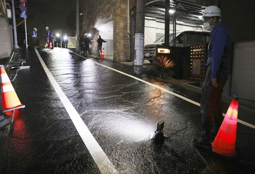 A road is soaked in water following an earthquake at a residential area in Tokyo, early Friday, Oct. 8, 2021. A powerful earthquake shook the Tokyo area on Thursday night, halting trains and subways. (Kyodo News via AP)