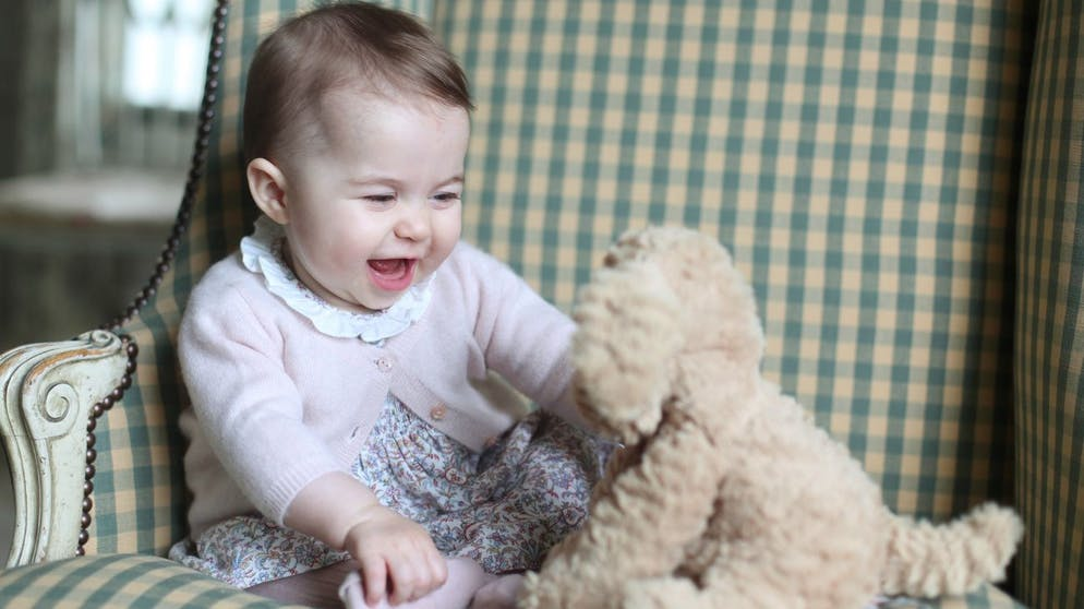 In this undated photo released Sunday Nov. 29, 2015, by Britain's Duke and Duchess of Cambridge, showing Princess Charlotte with her cuddly toy dog, at Anmer Hall in Sandringham, England. Princess Charlotte was born May 2, 2015, and the photo was taken by her mother, Kate Duchess of Cambridge, during November 2015. (Duchess of Cambridge via AP)