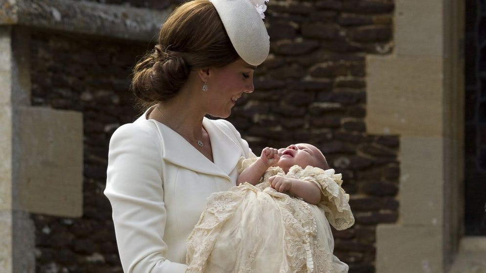 Britain's Kate the Duchess of Cambridge carries Princess Charlotte after taking her out of a pram as they arrive for Charlotte's Christening at St. Mary Magdalene Church in Sandringham, England, Sunday, July 5, 2015. (AP Photo/Matt Dunham, Pool)