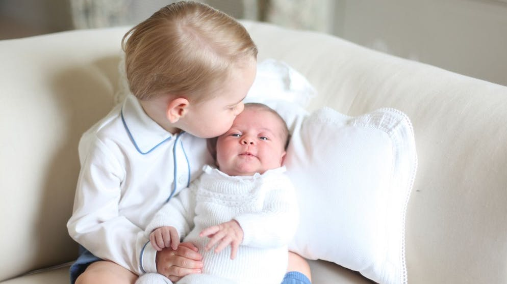 This image made available by Kensington Palace Saturday, June 6, 2015, taken by Kate, Duchess of Cambridge, at Anmer Hall, eastern England in mid-May 2015 shows Britain's Princess Charlotte, right, being held by her brother, 2-year-old, Prince George. Britain's royals have been photographed by some of the world's leading photographers. But Prince William and Kate are continuing a more informal tradition begun two years ago with the first official portrait of Prince George, taken by his grandfather Michael Middleton. Charlotte was born May 2 and is fourth in line to the throne. (Duchess of Cambridge via AP) MANDATORY CREDIT