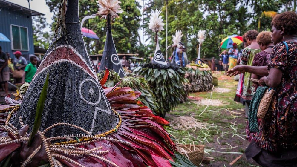 Mittlerweile sind alle Trauergäste inklusive 5 Tubuan anwesend, somit können die vom Taraui Clan ausgehängten Tabu zusammen mit Olivers gesamten Muschelgeldvermögen aufgebrochen und verteilt werden. Auch Lua Akila wird ein grosses Agogo (zu einem Rad gebundenes Tabu à 2500 Kina / 644 CHF) beisteuern. Seine anderen drei Agogo reserviert Lua für die anstehende Brautpreis-Zeremonie seines Sohnes.