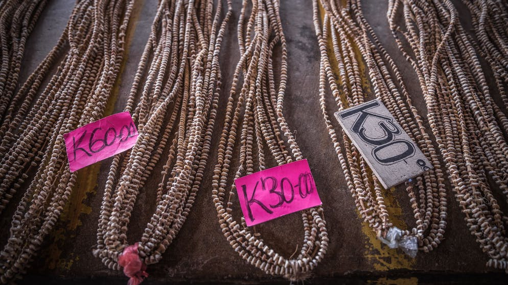 At Kokopo Market. Market ladies are selling Tabu Shell Money. When buying, the value of 1 Param is 6 Kina. When selling, the value of 1 Param is 5 Kina. The most common unit is 1 Param, which is an arm span of a Tolai (around 2 metres, hanging lose). 10 Params in Tolia Language is 1 Arip. The average size of a Agogo involves between 20 and 40 Arip or 200 – 400 Param.   1 Param (= 5 Kina) A person's arms spread out, one circle string which should reach from one hand to the other, hanging lose (not tight) with roughly 220 to 240 shells attached to the string. (can also be adjusted to a circle)   1 Arip = 10 Param combined (= 50 Kina) A person's arms spread out, 10 circle strings (Param) combined to a bundle of string circle which should reach from one hand to the other, hanging lose (not tight) with roughly 2'200 to 2'400 shells attached to the whole set.   1 Wheel/ Agogo (= roughly 500 Kina) Many strings combined to a wheel form roughly over 20'000 shells -> mostly used for bride price ceremonies. Different styles in the way the people put a wil together for easier identification of ownership. ________________ Reasons for people buying Tabu at the market: - Bride Price 'Warkukul' (paying off a women from her parents, so that she can marry) - Funeral and mourning ceremony 'Aminamai' (shell breaking among clans) - Birthday Gift  - Pig feasts (pigs are very precious in the villages) everyone contributes some shell money to get a share, usually 100 Kina (cash) and some Tabu in form of Param (shell money) - Compensations (simply to say sorry after a dispute) - Village court fees - such as paying off for the local justice – disuptes that are solved in the traditional house