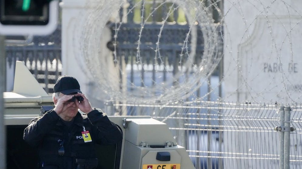 A police officer looks through a binoculars to guard the area in front of the 'Villa la Grange' ahead of the meeting of US President Joe Biden and Russian President Vladimir Putin at the villa, in Geneva, Switzerland, Wednesday, June 16, 2021. (AP Photo/Markus Schreiber)