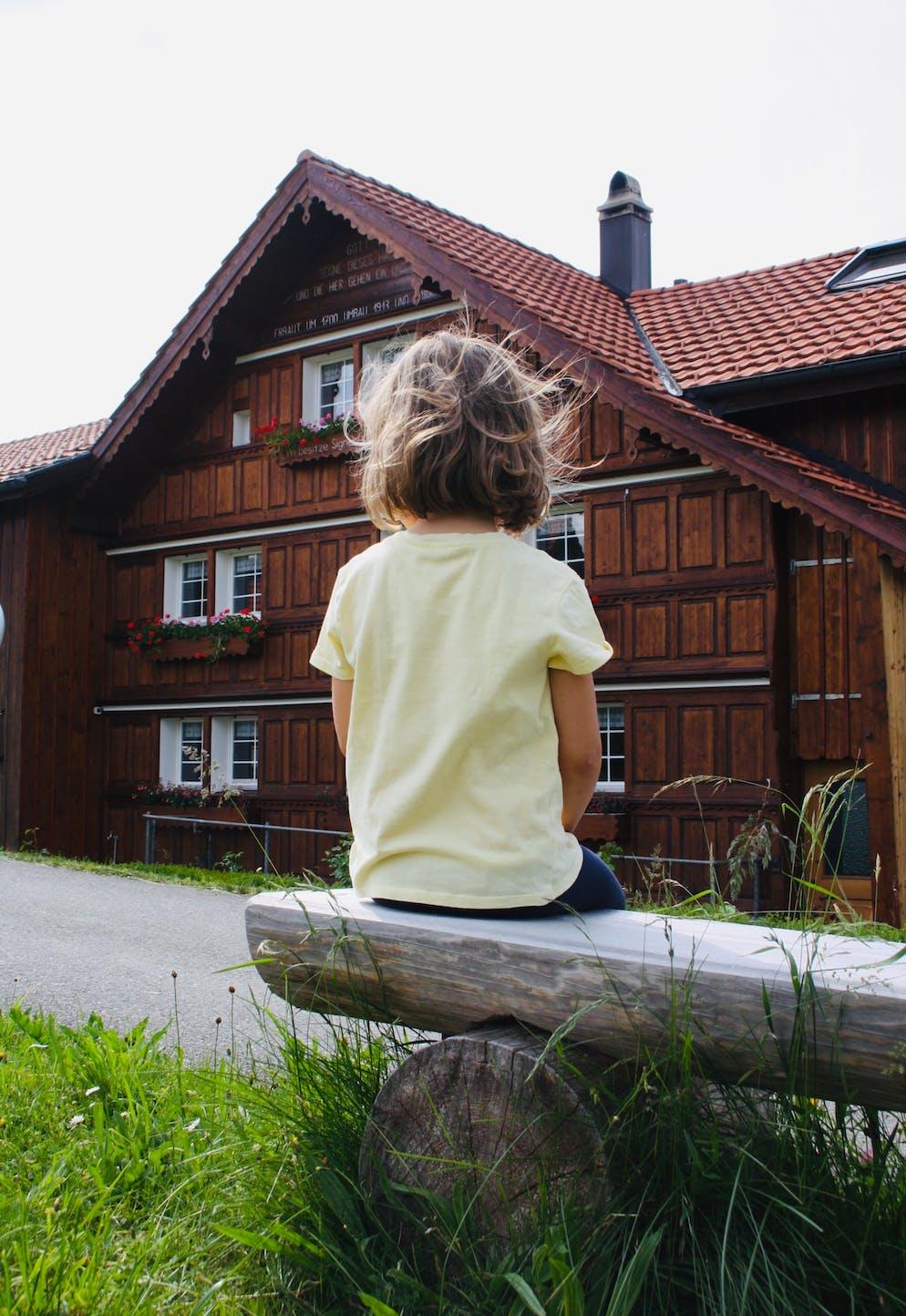 Tochter von Redaktorin Sulamith Ehrensperger sitzt vor Appenzeller Bauernhaus